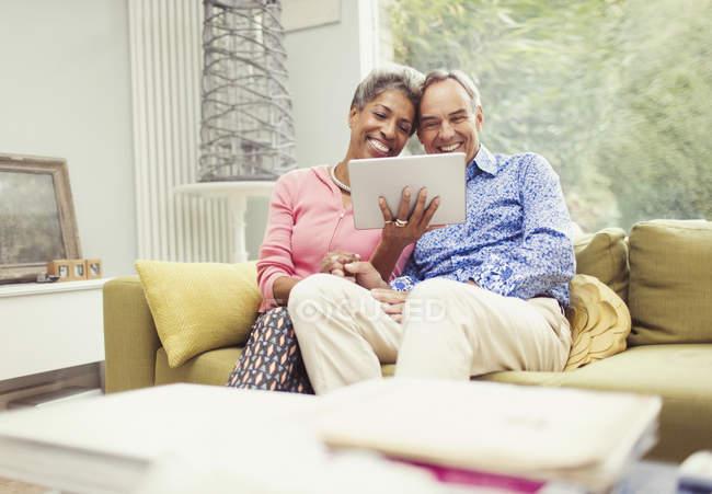 Smiling mature couple using digital tablet on living room sofa — Stockfoto