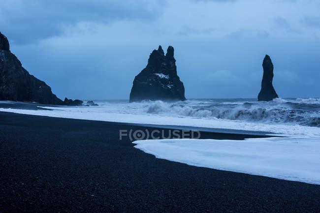 Felsformationen und stürmischen Ozean in der Abenddämmerung, Reynisdrangar, Vik, Island — Stockfoto