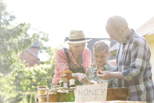 Grandparents and grandson selling honey at farmers market stall — Stock Photo