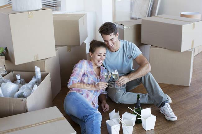 Profitant de champagne et chinois prennent de la nourriture dans la nouvelle maison — Photo de stock