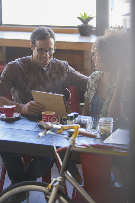 Friends sharing digital tablet in cafe — Stock Photo