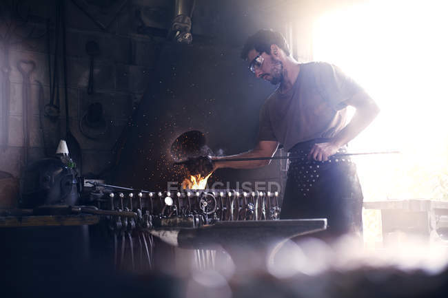 Blacksmith working at fire in forge — Stock Photo