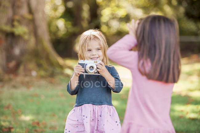 Toddler girls playing with camera in park — Stock Photo