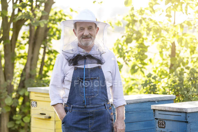 Portrait confident beekeeper in protective hat next to beehives — Stock Photo