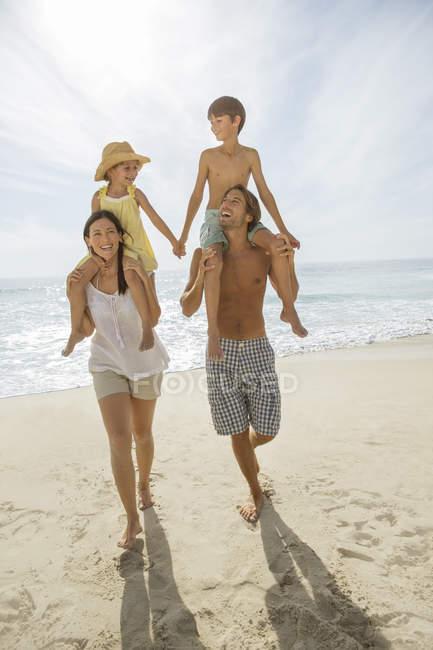 Padres cargando niños en hombros en la playa - foto de stock