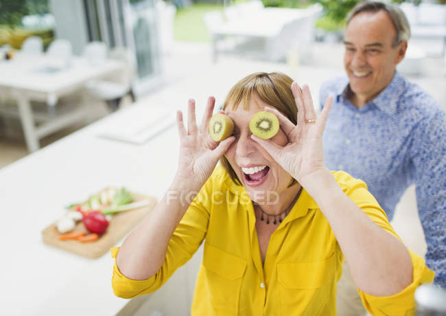 Portrait playful mature woman covering eyes with kiwi slices — Stockfoto