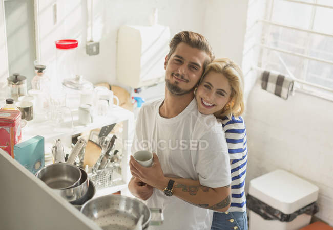 Portrait smiling young couple hugging in apartment kitchen — Stockfoto