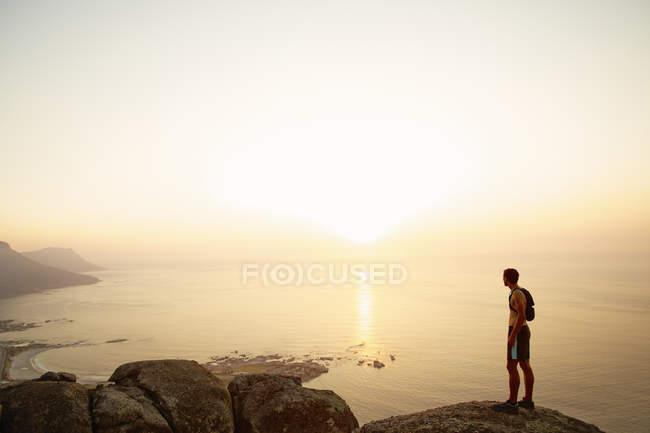 Runner su rocce guardando il tramonto vista sull'oceano — Foto stock