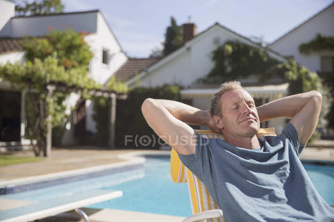 Happy caucasian man relaxing at poolside — Stock Photo