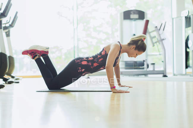Woman doing push-ups on knees at gym — Stock Photo