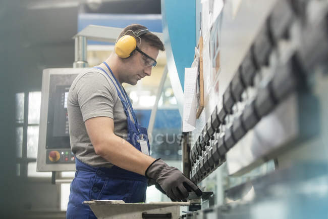 Worker in protective workwear working in factory — Stock Photo