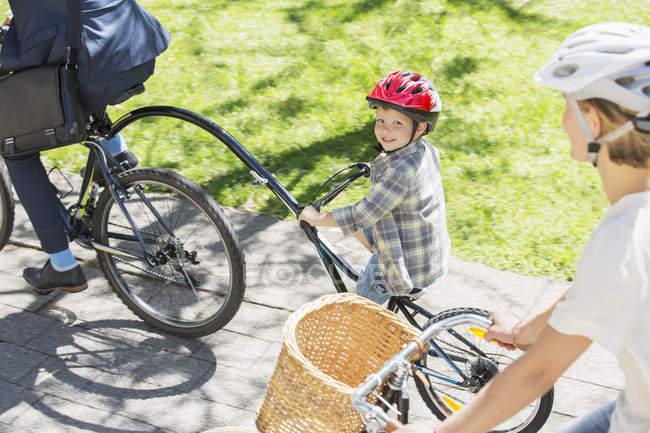 Портрет улыбающийся мальчик на тандеме велосипеде с отцом в парке — стоковое фото