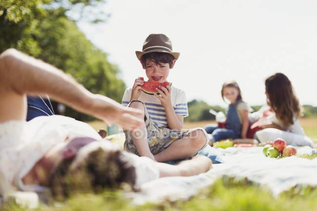 Улыбающийся мальчик ест арбуз на одеяле в солнечном поле — стоковое фото