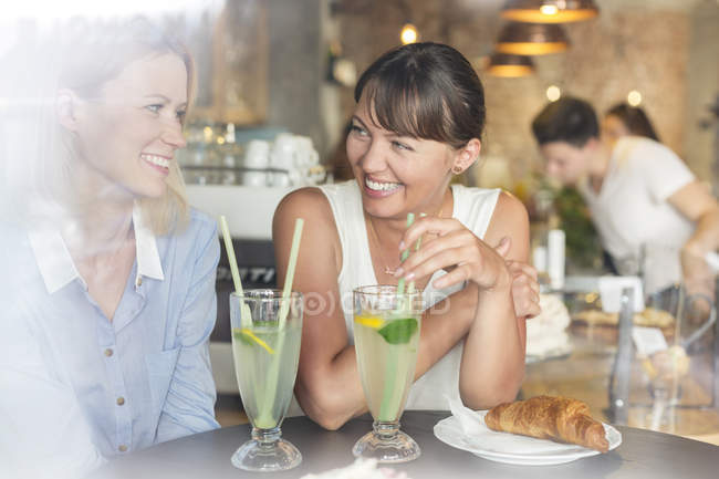 Smiling women drinking lemonade at cafe table — Stock Photo