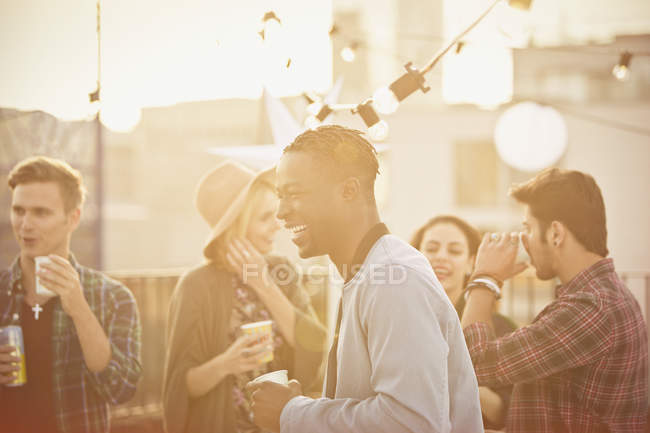 Young man laughing and drinking at rooftop party — Stockfoto