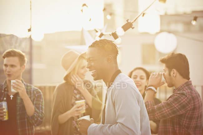 Молодой человек смеется и пьет на вечеринке на крыше — стоковое фото