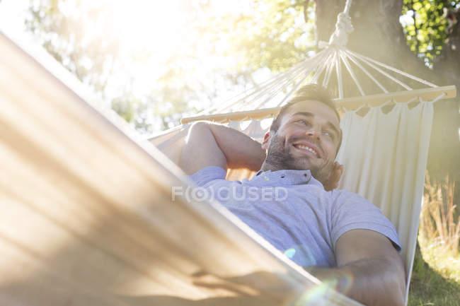 Улыбающийся молодой человек отдыхает в летнем гамаке — стоковое фото