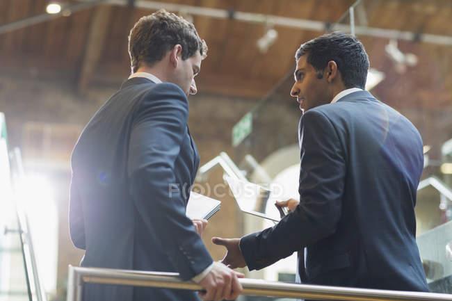 Бизнесмены с цифровыми планшетами разговаривают в офисе — стоковое фото