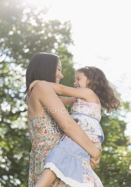 Affectionate mother holding and hugging daughter outdoors — Stock Photo