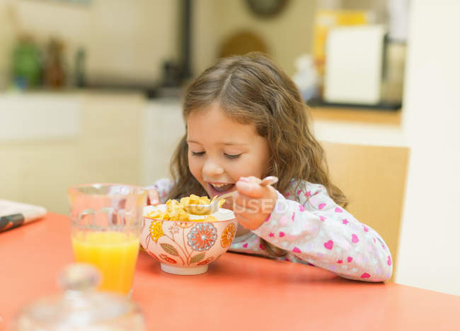 Девочка ест зерновые на стол завтрак — стоковое фото