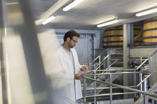Vintner in lab coat with clipboard in winery cellar — Stock Photo
