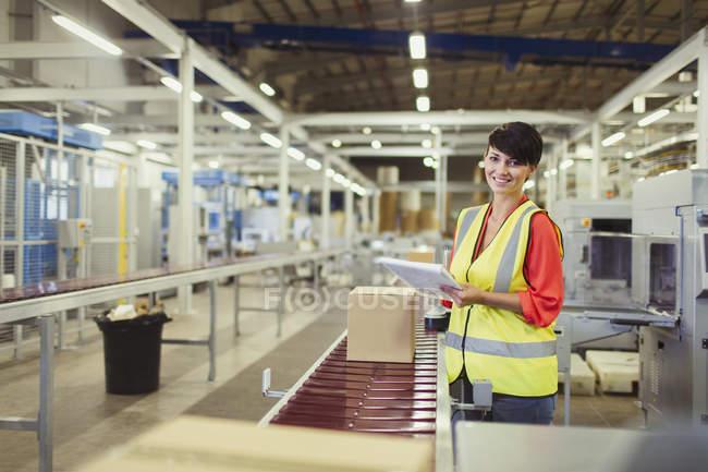 Портрет улыбающийся рабочий проверяет картонные коробки на конвейерной ленте производственной линии на заводе — стоковое фото