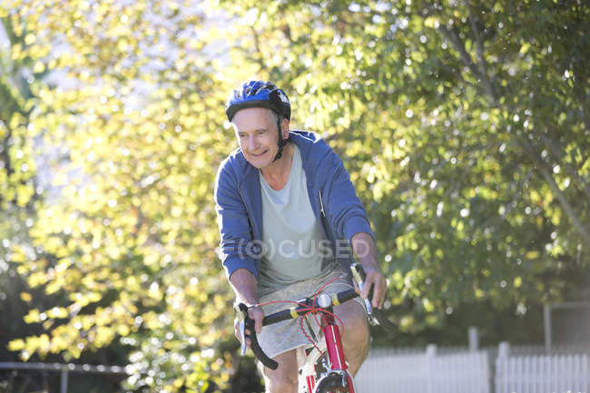 Senior man riding bicycle in park — Stock Photo