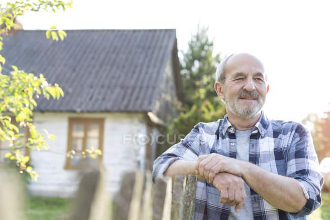Уверенный фермер, опирающийся на забор возле фермерского дома — стоковое фото