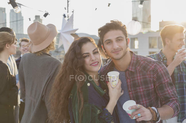 Portrait smiling young couple drinking at rooftop party — Stockfoto