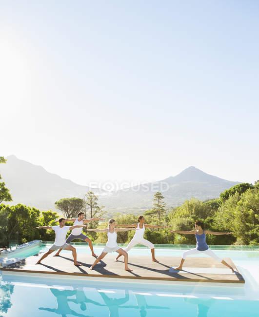 Jóvenes atractivos practicando yoga junto a la piscina - foto de stock