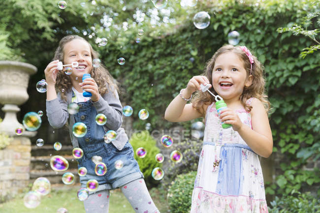 Carefree girls blowing bubbles in backyard — Stock Photo