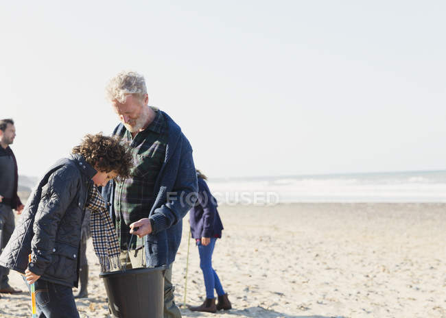 Multi-generation family clam digging on sunny beach — Stock Photo