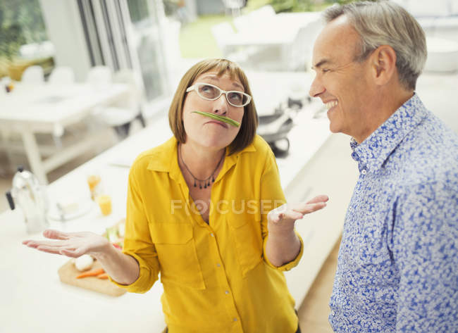 Playful mature woman with green bean mustache — Stockfoto