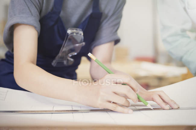 Carpenter drafting plans with pencil and ruler — Stock Photo