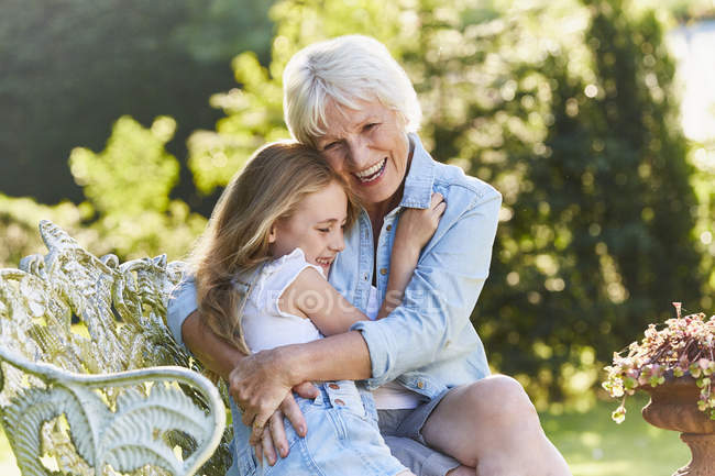 Grandmother and granddaughter hugging on garden bench — Stock Photo