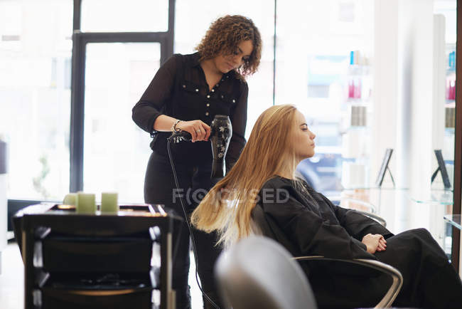 Hairdresser drying customers long hair in salon — Stock Photo