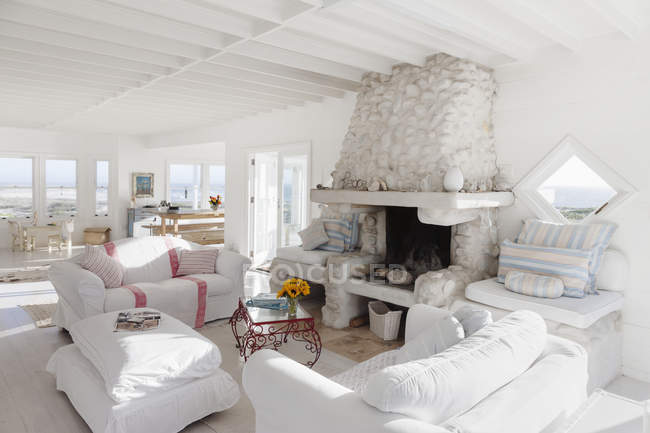 Sofas and fireplace in white living room — Stock Photo