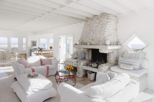 Диваны и камин в белой гостиной — стоковое фото