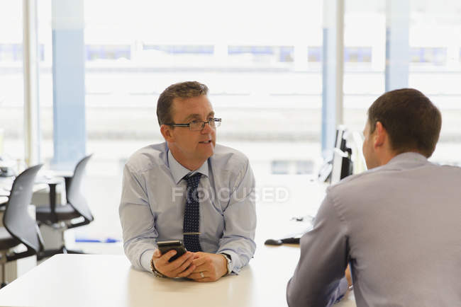 Businessmen talking together in modern office — Stock Photo