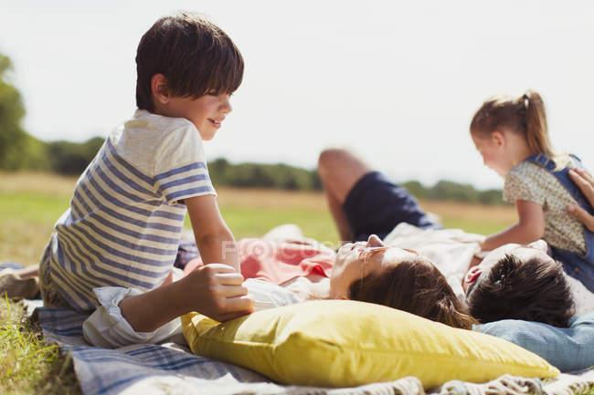 Família relaxando no cobertor no campo ensolarado — Fotografia de Stock