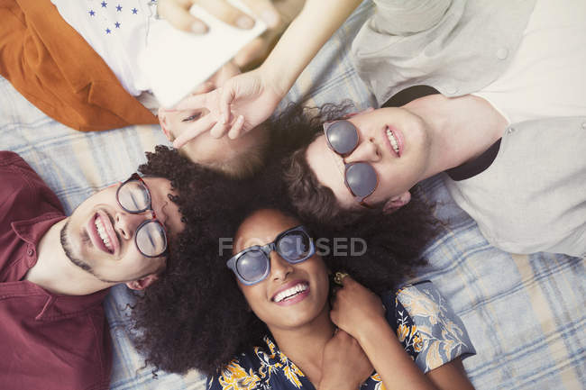 Overhead portrait smiling friends laying in circle on blanket — Stock Photo