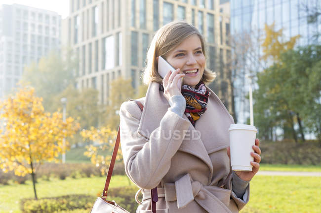 Smiling businesswoman with coffee talking on cell phone in city park — Stock Photo