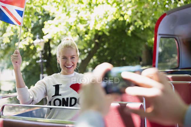 Жінка, розмахуючи британський прапор, були спрямовані на двоповерхового автобуса — стокове фото