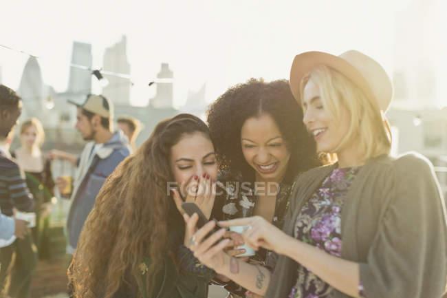 Молодые женщины смеются и пишут смс с мобильного телефона на вечеринке на крыше — стоковое фото