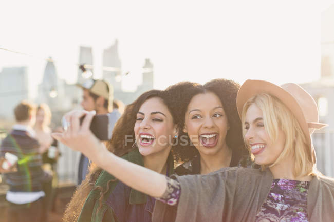 Enthusiastic young women taking selfie at rooftop party — Stock Photo