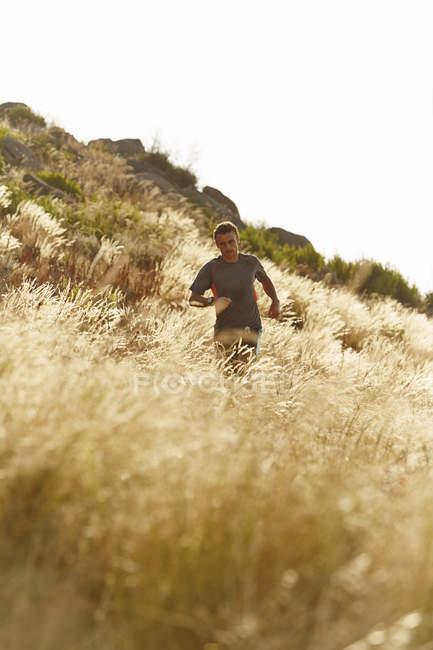Man running through tall sunny grass — Stockfoto