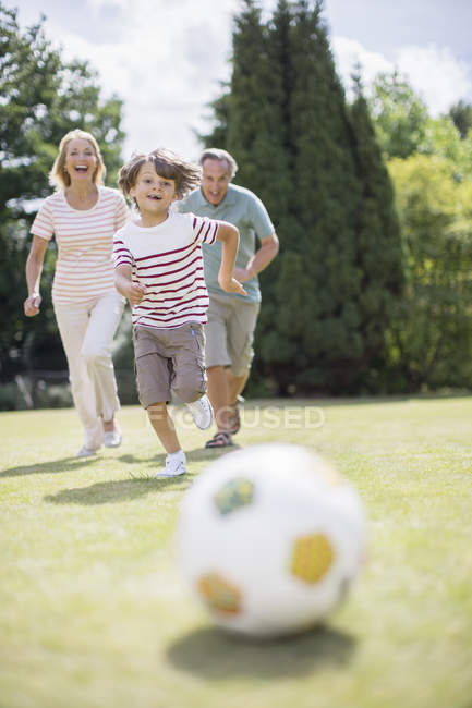 Happy grandparents and grandson playing soccer — Stock Photo