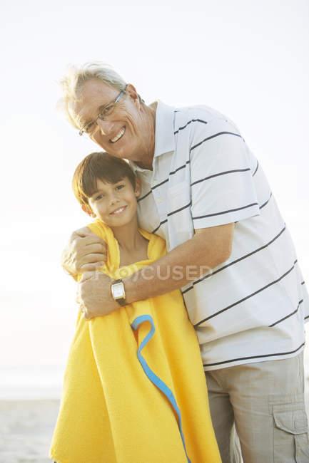 Дедушка обнимает внука на пляже — стоковое фото