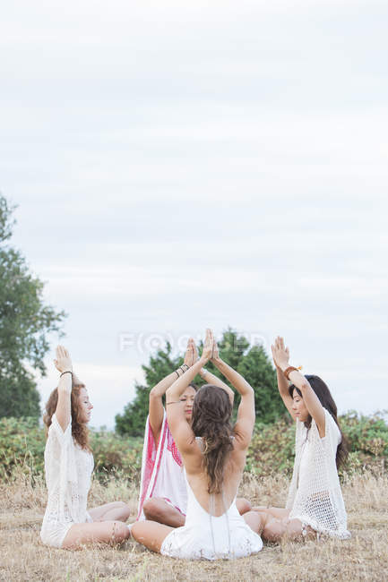 Boho women meditating with hands clasped overhead in circle in rural field — Stock Photo