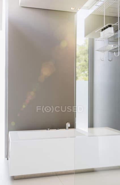 Bathtub and glass wall in modern bathroom — Stock Photo